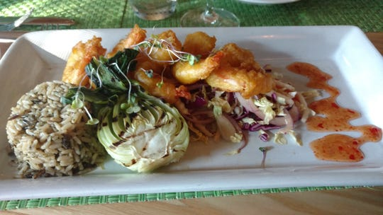At Citron Bistro, crispy, delightfully seasoned and lightly breaded fried shrimp tempura is served over a bed of vegetable slaw and accompanied by wild rice.