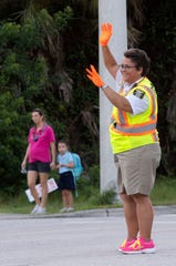 "Michelle Strunk, a Martin County Sheriff's Office traffic control officer, directs vehicles, students and their families, including Paula Hartwick (left) and her daughter, Hobe Sound Elementary School kindergartner Kyleigh Hartwick, on Thursday, Sept 19, 2019, outside of the school in Hobe Sound. Strunk is in her 28th year as a crossing guard for the school and the job is part of her family's legacy. ""My mom was the first ever crossing guard (at Hobe Sound Elementary School),"" Strunk said. ""That was a few bosses ago."""
