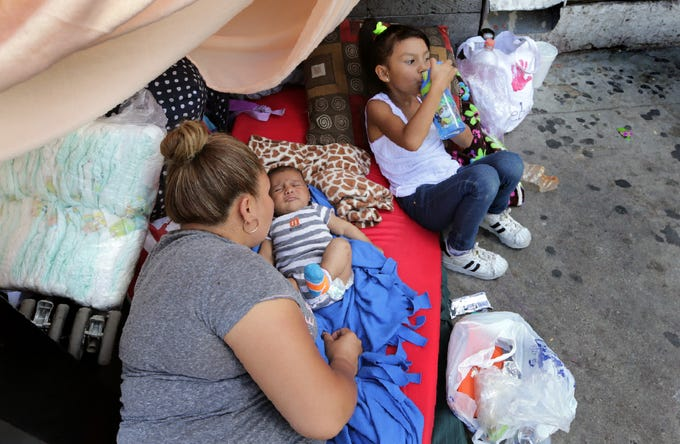 A mom tends to her two-month-old baby as he awakes once again in the streets of Juarez as his family awaits asylum in the United States. A group of almost 150 Mexican asylum seekers are camping out next to the Paso del Norte International Bridge as they wait to be called to their hearing.