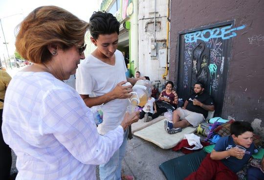 Maria Teresa Zorrilla and Edgar Zamora of Juarez serve burritos and agua de melon to Mexican asylum seekers camped out at the base of the Paso del Norte International Bridge Thursday.
