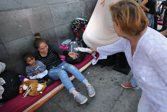 Maria Teresa Zorrilla of Juarez serves burritos and agua de melon to Mexican asylum seekers camped out at the base of the Paso del Norte International Bridge Thursday.