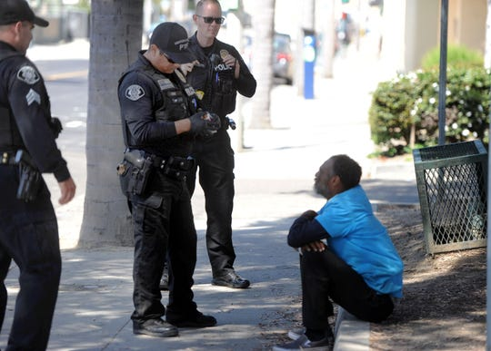Ventura police Sgt. Mike Anselmo, Officer Jaime Uribe and Cpl. Trenner Marchetti speak with Felipe, who is homeless, before he speaks with a Ventura County Behavioral Health community service coordinator. The position is embedded with police three days per week.
