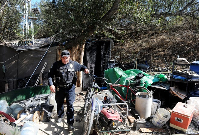 Michael Anselmo, sergeant, Ventura Police Department  walks through a homeless camp at the mouth of the Santa Clara River. The Ventura Police Department has a mental health services coordinator that assists officers five days a week.