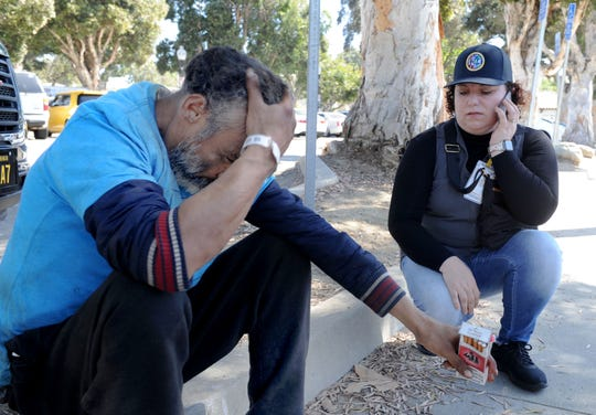 Felipe, who is homeless, gets help calling his mother from Diana Gasmi, a community services coordinator with Ventura County Behavioral Health. Three days a week, she is embedded with the Ventura Police Department's Patrol Task Force.
