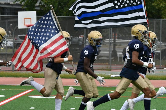 "The Yonkers Force football team takes to Tony DeMatteo Field at Roosevelt High School to face Ossining on Sept. 14, 2019, under the American and first-responder flags. The Force comprises students from Gorton, Roosevelt, Yonkers Montessori Academy and Yonkers high schools and is sponsored by the Yonkers Police Benevolent Association. A patch of the first-responder flag appears on the Force uniforms and Roosevelt senior Justin Broquadio bought a full-sized first-responder flag that he carries out to start each game. ""It's on our jerseys, we're representing the police, because they do so much for us in the community, so I thought I'd go and run out and pay respect to them. It's not a lot, but it's something that we could just give back to them."""