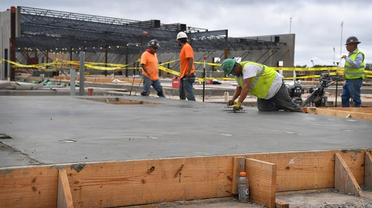Construction workers finish a slab of concrete at the Law Enforcement Center site adjacent to the Sprague Annex. Most of the construction trades on the project are local to the area.