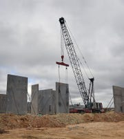 A crane is used to erect walls constructed of concrete and rigid foam insulation during the building of the Wichita County Law Enforcement Center.