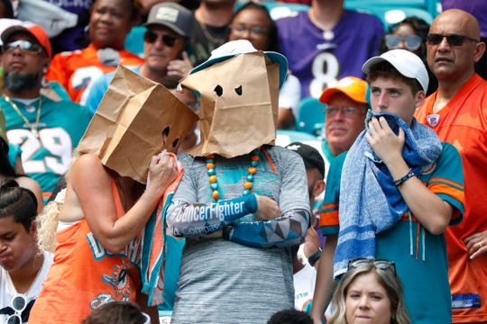 FILE - In this Sept. 8, 2019, file photo, Miami Dolphins fans shows his displeasure with the team during the first half at an NFL football game against the Baltimore Ravens, in Miami Gardens, Fla. The Dolphins look like the worst team in the NFL. (AP Photo/Wilfredo Lee, File)