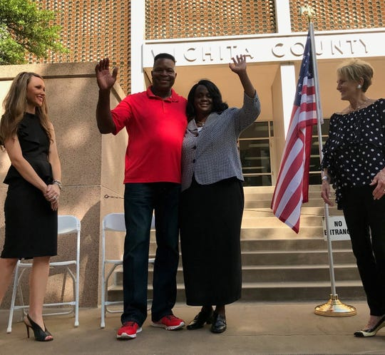 Annetta Pope, third from left, and husband Calvin Dotson, second from left, wave to the crowd after her announcement she is running for Precinct 1, Place 1 justice of the peace for Wichita County on Thursday on the steps of the Wichita County Courthouse.