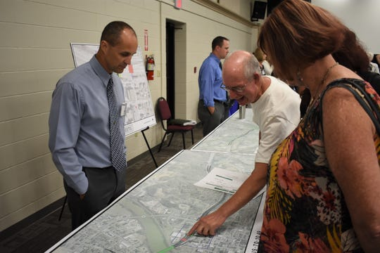 Doug Morgan of ODOT listens as a citizen who attended the meeting discusses the project while pointing toward the I-70 bridge over Fifth Street.