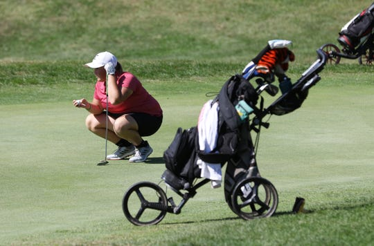 Crooksville's Riley McKenzie lines up a putt during the Muskingum Valley League Girls Tournament at Eaglesticks Golf Club in Zanesville on Thursday. McKenzie finished as the tournament medalist with a 75 and helped the Ceramics claim the team title.