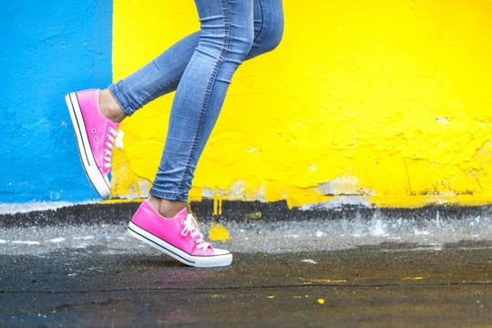 Pink sneakers worn with blue jeans against a colorful street wall.