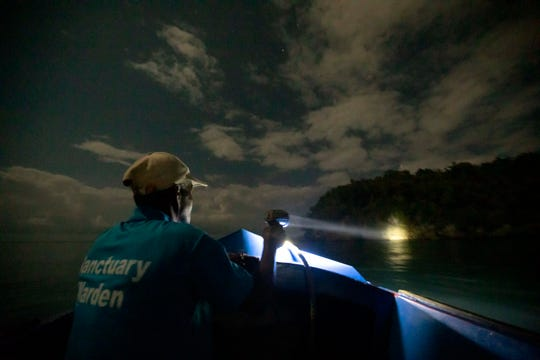 """White River Fish Sanctuary warden Donald Anderson shines a spotlight on the coast looking for illegal fishermen while patrolling the no-take zone under moonlight in Ocho Rios, Jamaica on Feb. 15, 2019. The patrols carry no weapons, so they must master the art of persuasion. And they often meet resistance. """"They threaten us and they give you trouble in the reef,"""" Anderson said."""