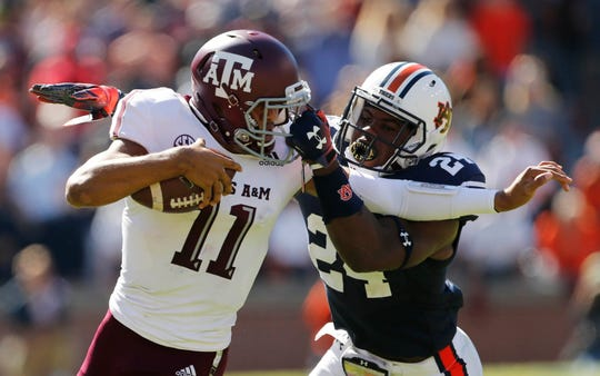 Texas A&M quarterback Kellen Mond is grabbed by Auburn defensive back Daniel Thomas during their game at Jordan-Hare Stadium in 2018.