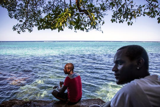 Fishermen Damian Brown, left, and Ian Hurlock, sit by the reef where they grew up swimming and fishing in Stewart Town, Jamaica on Feb. 15, 2019. Brown has been caught twice fishing inside the nearby no-take zone and now relies more on night fishing, which is banned, to make up for his wages impacted by the sanctuary's restrictions.