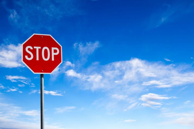Stop sign and blue sky with clouds.