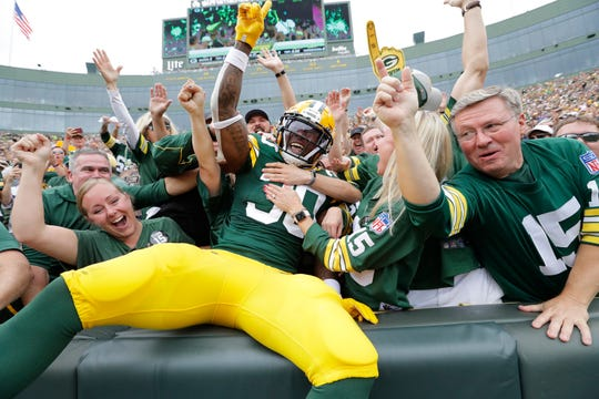 Green Bay Packers running back Jamaal Williams (30) celebrates scoring a touchdown with a Lambeau Leap in the first quarter during their football game Sunday, September 15, 2019, at Lambeau Field in Green Bay, Wis.