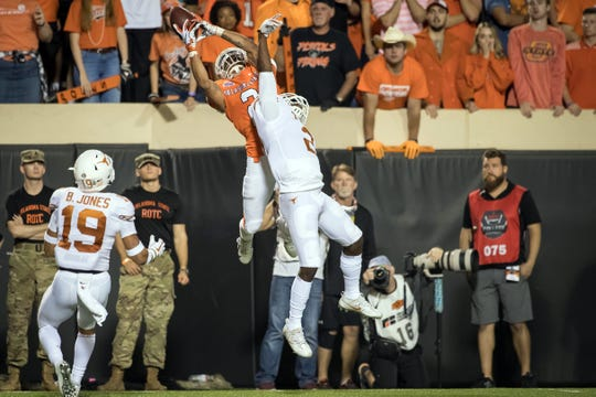Oklahoma State wide receiver Tylan Wallace makes a catch while defended by Texas defensive back Brandon Jones during their 2018 game at Boone Pickens Stadium.