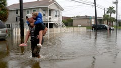 Terry Spencer carries his daughter, Trinity, through high water on 59th Street near Stewart Road in Galveston, Texas, Wednesday, Sept. 18, 2019.