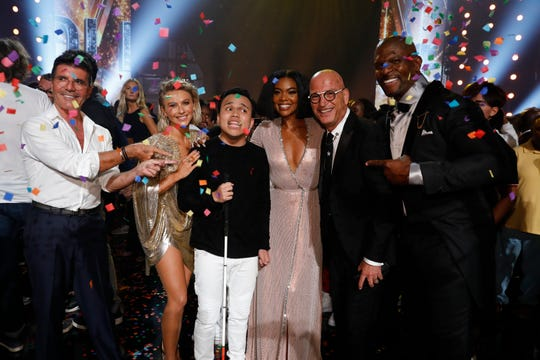 As confetti falls on the Dolby Theatre stage, 'America's Got Talent winner Kodi Lee, third from left, poses with judges Simon Cowell, left, Julianne Hough, Gabrielle Union and Howie Mandel and host Terry Crews.