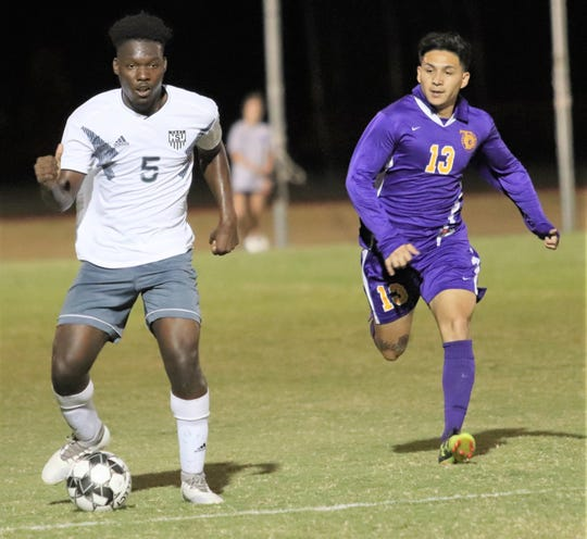 HSU's Mackenson Cadet, left, dribbles the ball while a defender gives pursuit during a Cowboys soccer game.