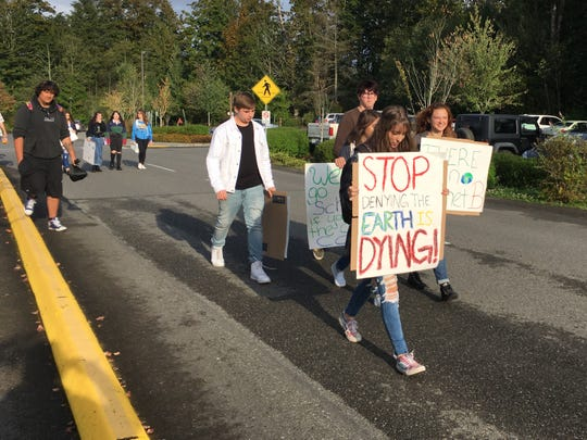 Students from Kingston High School in North Kitsap School District joined the global youth walkout to call attention to climate change on Friday.