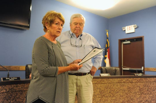 "Black Mountain Vice Mayor Maggie Tuttle reads a proclamation declaring Oct. 5 ""Beacon Blankets Day,"" as Tedd Smith looks on."