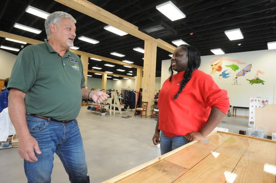 Black Mountain Home for Children President Tom Campbell talks to N'Dia Lee, a resident at the home's independent living program and employee at the Mountain Home Thrifts store. The home will unveil the store, and its Thirteen Pennies Cafe, on Oct. 12.