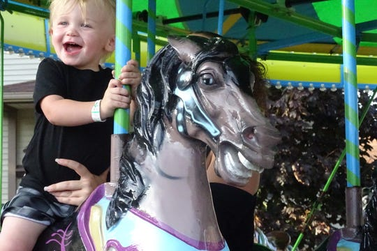 Roman Castle, 2, enjoys a merry-go-round during the Crestline Harvest Festival on Thursday. His mom, Chado Horton, was holding him tight.