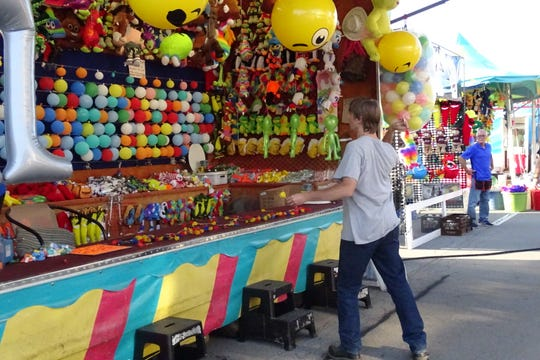 A young man tosses a dart at a carnival game Thursday at the Crestline Harvest Festival.