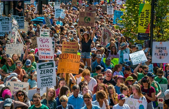 Center, standing on a bench, University of Vermont student Sophia Carlat of Newburyport, Mass., joins thousands packing Church Street in front of Burlington City Hall on Friday, Sept. 20, 2019, for the Vermont Climate Strike Rally, part of the Global Climate Strike worldwide to draw attention to climate change.
