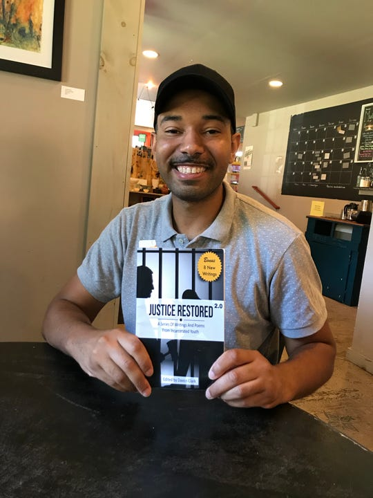 Davon Clark holds a copy of 'Justice Restored: A Series of Writings and Poems from Incarcerated Youth.' He will read selections from the book at the Collingswood Book Festival Oct. 5.