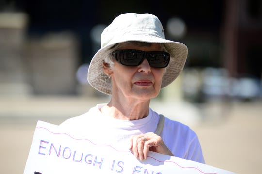 Marianna Carney holds a sign at a gun control rally outside the Ohio Statehouse on Wednesday, Sept. 18, 2019.