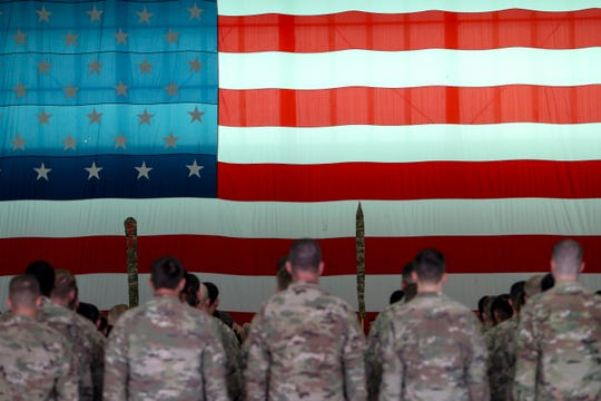 An American flag drapes from one side of the room where soldiers stand in formation during a welcome home ceremony for Screaming Eagles soldiers from the 1st Brigade Combat Team returning home at Army Airfield in Fort Campbell, KY., on Thursday, Sept. 19, 2019.