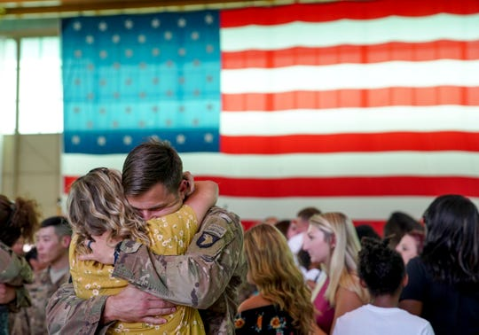 Soldiers embrace family and friends after being dismissed to mingle during a welcome home ceremony for Screaming Eagles soldiers from the 1st Brigade Combat Team returning home at Army Airfield in Fort Campbell, KY., on Thursday, Sept. 19, 2019.