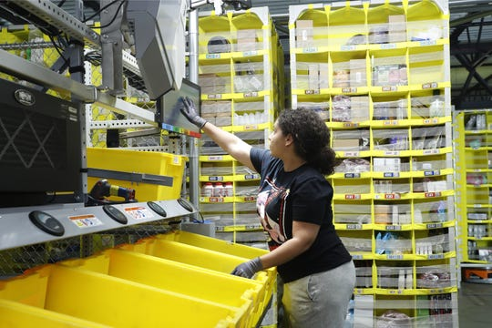 In this June 26, 2019, file photo a worker sorts through items and places orders at the Amazon Fulfillment Center in Staten Island in New York. Amazon hopes to open a similar fulfillment center on the site of the old Pontiac Silverdome in Oakland County. (AP Photo/Kathy Willens)