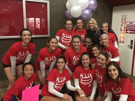 Nichole Wouters, in black, poses with the Clinton Twp. Chippewa Valley volleyball team in 2017 during coaches appreciation night.