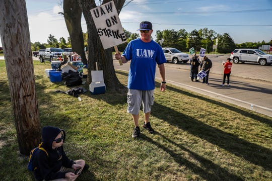 Erik Bond, 41, of Grand Blanc walks up to his son, Maximus, while striking together as a family outside of the General Motors Flint assembly plant on the fourth day of the nationwide strike.