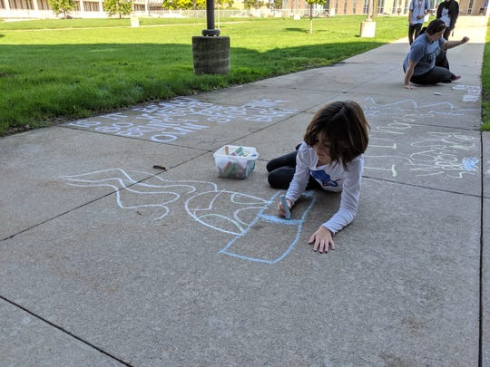 """Lucia Caramia, 8, of Lathrup Village, creates chalk art on the sidewalks at Henry Ford College in Dearborn Friday, Sept. 20, 2019 , as her mother, Shine Caramia, does the same in the background.  Their art was in conjunction with """"climate strikes"""" organized at the college, across Michigan, the U.S. and the globe, to help bring awareness and spur action on climate change."""