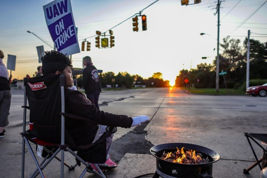 Flint Regina Knuckles, 46, warms up on the fourth day of the UAW's nationwide strike against General Motors on Thursday, September 19, after stalling contract negotiations in Flint, Michigan, near a fire pit, in 2019.