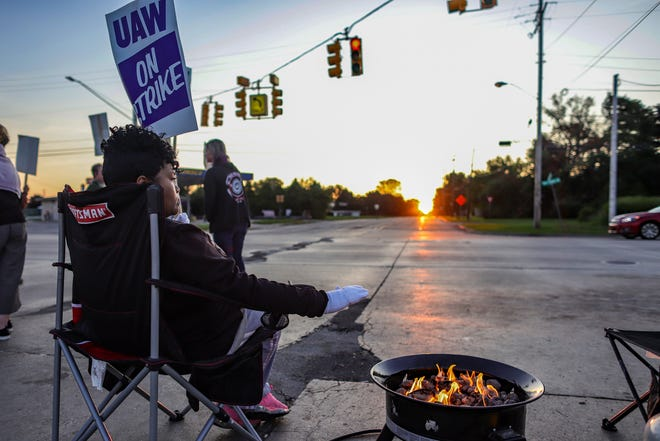 Regina Knuckles, 46, of Flint stays warm next to a fire pit on the fourth day of the nationwide strike of UAW strike against General Motors after stalled contract talks in Flint, Mich. on Thursday, Sept. 19, 2019.