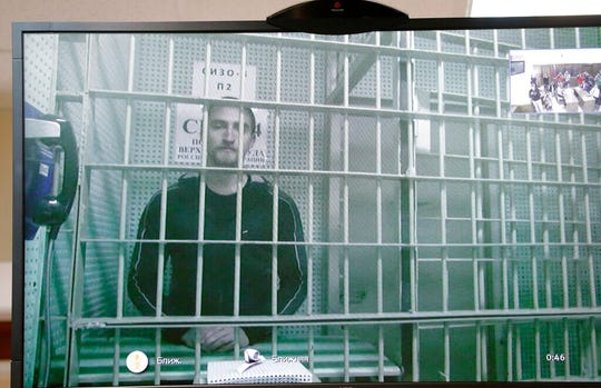 Actor Pavel Ustinov, who was earlier sentenced to 3 and a half years in prison for assaulting police at the July 27 rally, is shown on a TV screen as he listens to the decision of the court of cassation while in remand prison in Moscow, Russia, Friday, Sept. 20, 2019. Ustinov has been released from pre-trial detention following a massive outcry and an appeal is scheduled for Sept. 26.