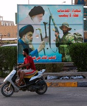 In this Wednesday, Sept. 18, 2019 photo, a billboard shows Shiite spiritual leaders, and a volunteer fighter from the Iran-backed Popular Mobilization Forces killed in Iraq fighting Islamic State militants, in Baghdad, Iraq. As the United States and Israel step up their efforts to contain Iran, countries in Tehran's orbit are feeling the heat.