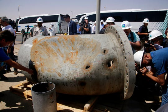 In this photo opportunity during a trip organized by Saudi information ministry, media film holes caused by fragments of a missile in a damaged pipe in the Aramco's Khurais oil field.
