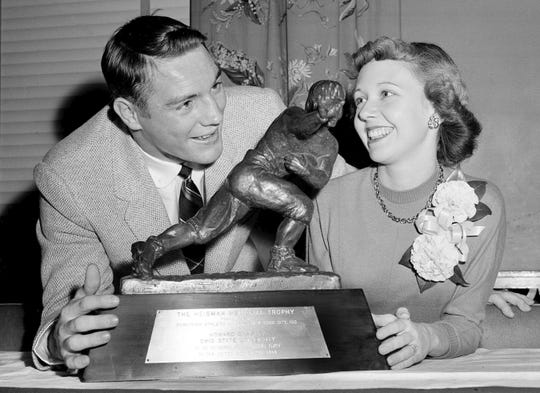 "In this Dec. 8, 1955, file photo, All-America Howard ""Hopalong"" Cassady, halfback for Ohio State, and his wife, Barbara, pose with the Heisman Trophy awarded to Cassady in New York."