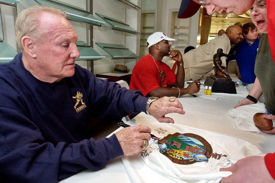 "In this Jan. 14, 2004, file photo, Howard ""Hopalong"" Cassady, Heisman Trophy winner from Ohio State in 1955, autographs a Hula Bowl T-shirt for a fan in Kaanapali, Hawaii."