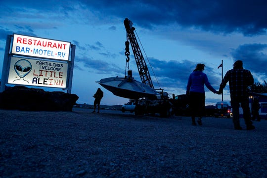 "People walk near the Little A'Le'Inn during an event inspired by the ""Storm Area 51"" internet hoax, Thursday, Sept. 19, 2019, in Rachel, Nev. Hundreds have arrived in the desert after a Facebook post inviting people to ""see them aliens"" got widespread attention and gave rise to festivals this week."