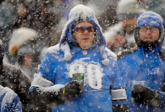 A snow-covered Lions fans looks on as Detroit loses.