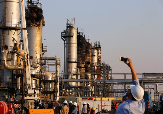 During a trip organized by Saudi information ministry, a cameraman films Aramco's oil processing facility after the recent Sept. 14 attack in Abqaiq, near Dammam in the Kingdom's Eastern Province, Friday, Sept. 20, 2019.