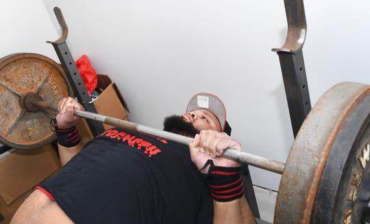 Paraplegic power lifter Antonio Martin practices the bench press at his home in Utica.